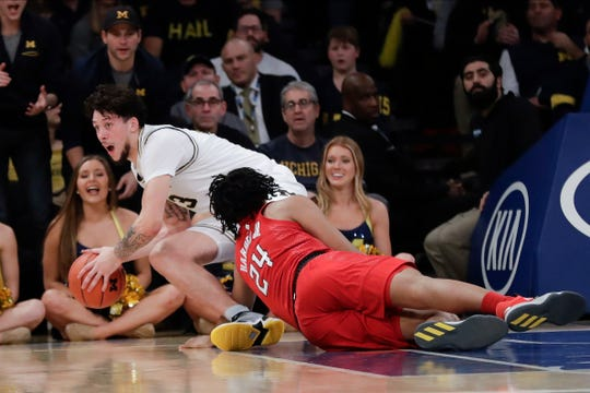 Michigan's Brandon Johns Jr. fights for control of the ball with Rutgers' Ron Harper Jr.