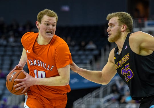 Evansville's Evan Kuhlman (10) drive the lane under pressure from Northern Iowa's Justin Dahl (15) as the Evansville Purple Aces play the league leading Northern Iowa Panthers at the Evansville Ford Center Saturday afternoon, February 1, 2020.
