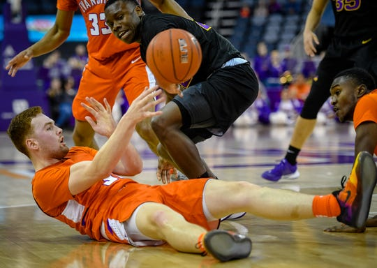 Evansville's Noah Frederking (30) passes the ball after a fall under pressure from Northern Iowa's Antwan Kimmons (22) as the Evansville Purple Aces play the league leading Northern Iowa Panthers at the Evansville Ford Center Saturday afternoon, February 1, 2020.