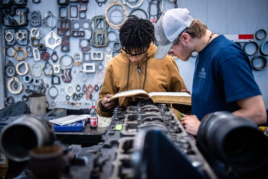 Donte Foster and Griffin Potter, of Greenville Tech's Diesel Equipment Technology program reference a manual while working on an engine during a class Thursday, January 30, 2020.
