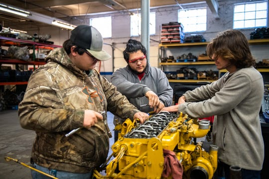 Seth Anglin, Eric Vazques, and Ryan Newton, of Greenville Tech's Diesel Equipment Technology program work on an engine during a class Thursday, January 30, 2020.