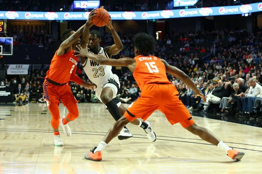 Feb 1, 2020; Winston-Salem, North Carolina, USA; Wake Forest Demon Deacons guard Chaundee Brown (23) drives to the basket against Clemson Tigers guard Al-Amir Dawes (2) and guard John Newman III (15) during the first half at Lawrence Joel Veterans Memorial Coliseum. Mandatory Credit: Jeremy Brevard-USA TODAY Sports