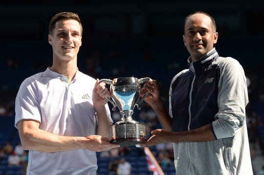 Rajeev Ram of the United States and Joe Salisbury of Great Britain hold aloft the championship trophy following their Men's Doubles Finals match against Max Purcell of Australia and Luke Saville of Australia on day fourteen of the 2020 Australian Open at Melbourne Park on February 02, 2020 in Melbourne, Australia.