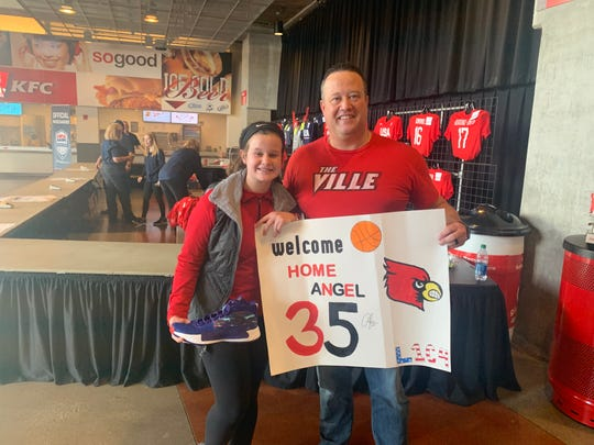 Left, Gracie Zutterman, poses with her father, Rich Zutterman, holding a sign she made and a shoe signed by Angel McCoughtry.