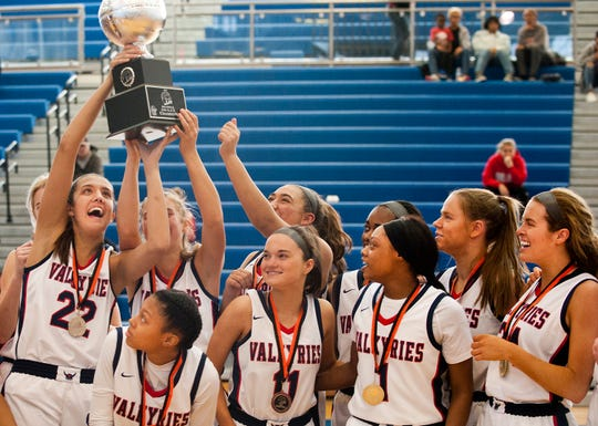 Sacred Heart center-forward Kristen Clemons holds the Girls Louisville Invitational Tournament championship trophy in the air as the team celebrates its 67-56 victory over Manual. Feb. 02,  2020
