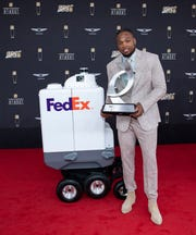 Tennessee Titans' running back Derrick Henry standing with FedEx's same-day delivery bot, Roxo. The bot helped deliver the Ground Player of the Year to Henry at the 9th annual NFL Honors in Miami.