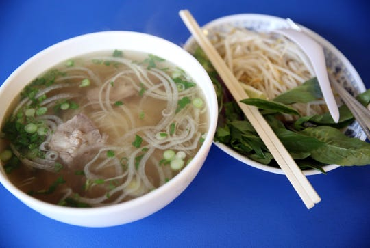 The noodle-and-broth bowl pho is served with garnishes such as fresh basil, bean sprouts and jalapeno slices that are added a bit at a time so the broth doesn't cool too quickly.
