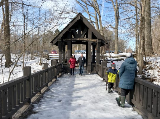 People enjoy the mild temperatures at Grant Park's Seven Bridges Trail in South Milwaukee on Sunday.