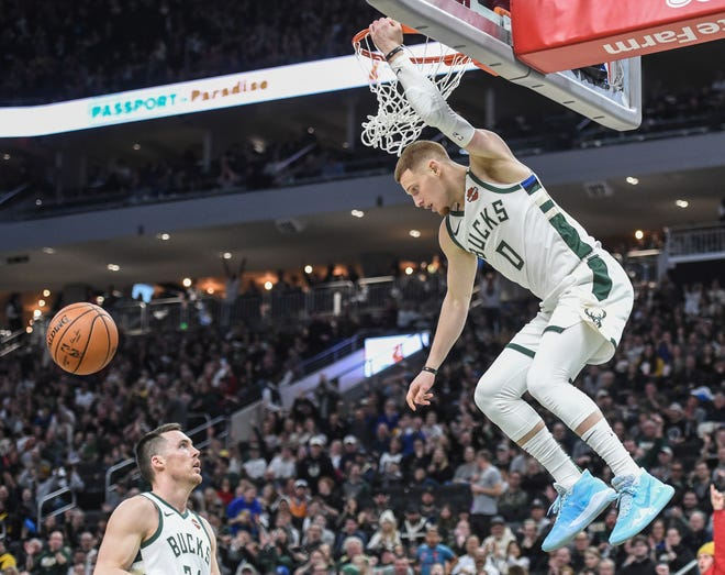 Bucks guard Donte DiVincenzo gets some hang time after capping off a fast break with a dunk against the Suns in the third quarter.
