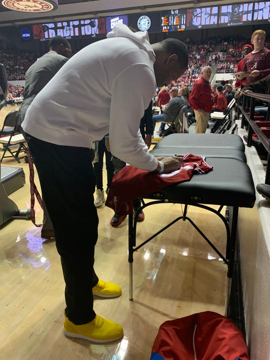 Former Alabama basketball player and NBA player Robert Horry signs a replica of his Crimson Tide jersey for a fan during his visit to Coleman Coliseum on Saturday as part of the 30-year anniversary of Alabama's 1989-90 team for the first of back-to-back Sweet 16 appearances that season. (Photo by Alex Byington/Montgomery Advertiser)