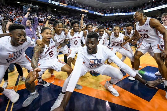 Auburn center Babatunde Akingbola (center) and teammates celebrate after a 75-66 win over Kentucky on Saturday, Feb. 1, 2020, in Auburn, Ala.