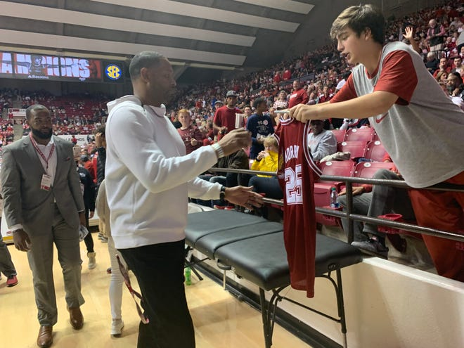 Former NBA and Alabama basketball player Robert Horry signs a replica of his Crimson Tide jersey for a fan during his visit to Coleman Coliseum on Saturday as part of the 30-year anniversary of Alabama's 1989-90 team for the first of back-to-back Sweet 16 appearances that season. (Photo by Alex Byington/Montgomery Advertiser)