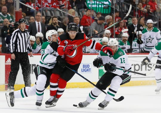 New Jersey Devils center Blake Coleman (20) plays the puck against Dallas Stars defenseman Esa Lindell (23) and center Radek Faksa (12) during the second period of an NHL hockey game Saturday, Feb. 1, 2020, in Newark, N.J. (AP Photo/Noah K. Murray)