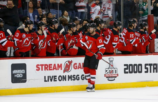 New Jersey Devils center Kevin Rooney (16) celebrates with teammates after scoring a goal against the Dallas Stars during the first period of an NHL hockey game Saturday, Feb. 1, 2020, in Newark,N.J. (AP Photo/Noah K. Murray)