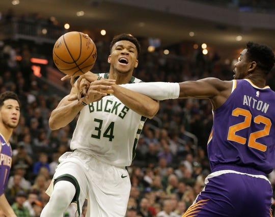 Milwaukee Bucks' Giannis Antetokounmpo (34) drives against Phoenix Suns' Deandre Ayton (22) during the first half of an NBA basketball game Sunday, Feb. 2, 2020, in Milwaukee. (AP Photo/Jeffrey Phelps)