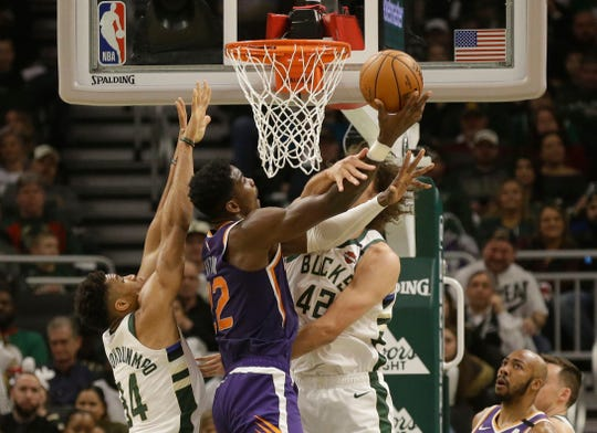Phoenix Suns' Deandre Ayton (22) shoots against Giannis Antetokounmpo, left, and Robin Lopez during the first half of an NBA basketball game Sunday, Feb. 2, 2020, in Milwaukee. (AP Photo/Jeffrey Phelps)