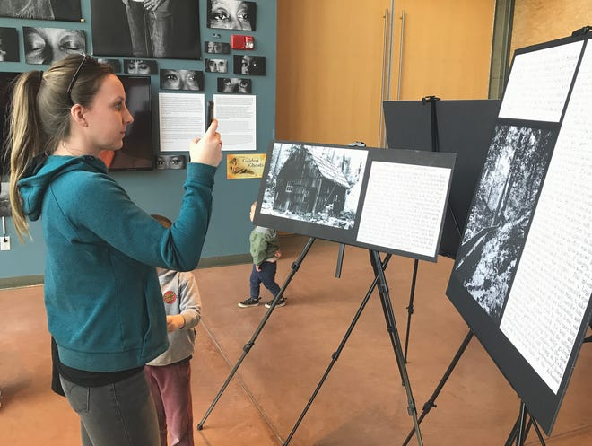 """Nicole Regalado of Lakehead photographs displays at the """"Voices of the Golden Ghosts"""" museum exhibit at Turtle Bay Exploration Park on Saturday, Feb. 1, 2020. Regalado took the pictures so she could have more time to read the text at home."""