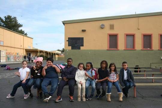 In this Jan. 27, 2020, photo, students at Lake Elementary School in San Pablo, Calif., sit on a bench in the schoolyard. The school was built in the 1950s and still has its old linoleum tiles that contain asbestos and other potentially harmful relics of the past. Proposition 13, the only statewide measure on the March 3 ballot, would create a $15 billion bond to build, repair and modernize schools, from kindergarten through public colleges and universities. (AP Photo/Jocelyn Gecker)