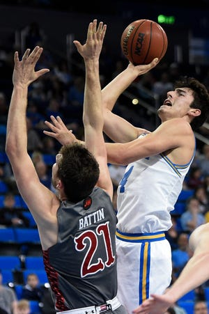 Jaime Jaquez Jr. shoots over Riley Battin during UCLA's victory over Utah on Sunday. Jaquez, a Camarillo High graduate who is third on the all-time scoring list in Ventura County high school history, finished with 18 points. Battin, an Oak Park High graduate who is first on the county's all-time list, led Utah with 14 points.