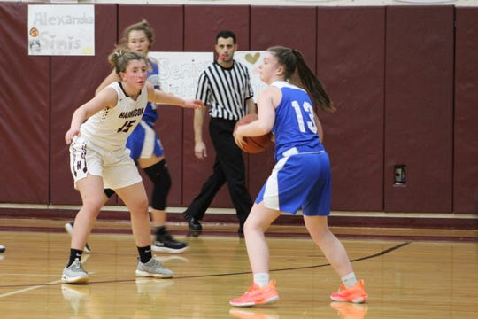 Mahopac's Julie DeBrocky scans the floor before delivering a pass, while Harrison's Victoria Lendino covers her.
