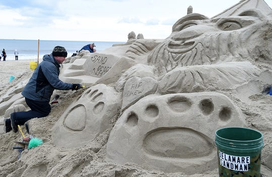 The Sand Bears put the finishing touches on a sand sculpture Sunday morning before the Polar Bear Plunge in Rehoboth Beach.