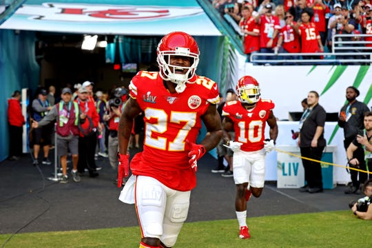 Kansas City Chiefs defensive back Rashad Fenton (27) and wide receiver Tyreek Hill (10) run onto the field at Hard Rock Stadium.