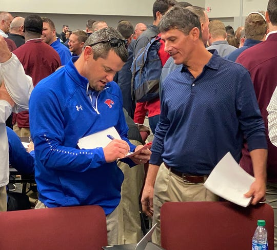 Cooper head coach Aaron Roan, left, and Wylie head coach Clay Martin talk about their schedules at the Birdville ISD Fine Arts/Athletics Complex in North Richland Hills on Monday The Cougars and Bulldogs will continue playing each other in 2020 and 2021. The UIL released the districts for 2020-22 as coaches met to set their schedules for the next two years.