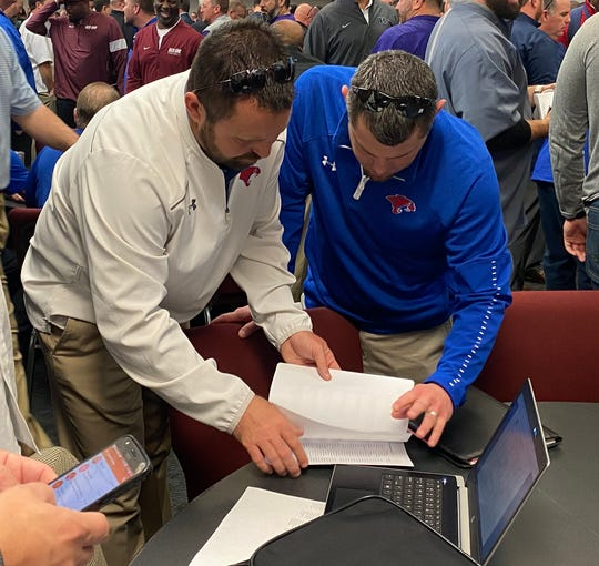 Cooper head coach Aaron Roan, right, and assistant coach Scott Stewart discuss their new district and schedule at the Birdville ISD Fine Arts/Athletics Complex in North Richland Hills.
