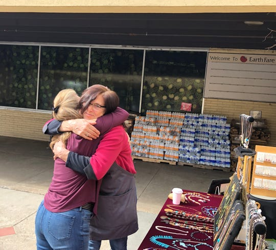 Jewelry vendor Michelle Blake, left, gives Earth Fare employee Lindy Paddock a hug outside the Westgate store on Feb. 3, 2020. Paddock says employees found out Monday morning the store would close, along with all of Earth Fare's locations.