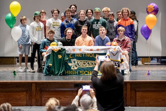 Reynolds senior Cooper Ingle takes photos with his teammates after signing a letter of intent to play baseball for Clemson University at Reynolds High School on Feb. 3, 2020.