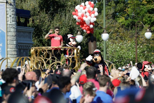 Super Bowl MVP Kansas City Chiefs quarterback Patrick Mahomes stands next to Mickey Mouse and waves to fans during a parade at the Magic Kingdom theme park at Walt Disney World, Monday, Feb. 3, 2020, in Lake Buena Vista, Fla. (AP Photo/John Raoux)