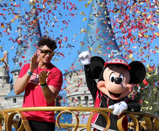 Under a shower of confetti, Kansas City Chiefs quarterback Patrick Mahomes, left, responds to cheering fans with Mickey Mouse during a parade in the team's honor at the Magic Kingdom at Walt Disney World, in Lake Buena Vista, Fla., Monday, Feb. 3, 2020. (Joe Burbank/Orlando Sentinel via AP)