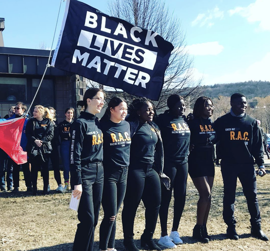 Students leaders from Racial Alliance Committee at Champlain Valley Union High School pose in front of a Black Lives Matter flag. The flag was raised in April 2019 and stayed up for 30 days.