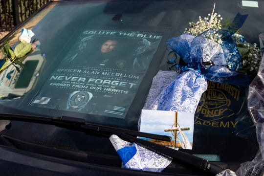 A makeshift memorial was setup around a police car parked outside the Corpus Christi Police Department to honor fallen Officer Alan McCollum on Monday, Feb. 3, 2020.