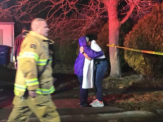 Two people embrace near the scene of a house fire on Medley Lane in Willingboro on Sunday night.