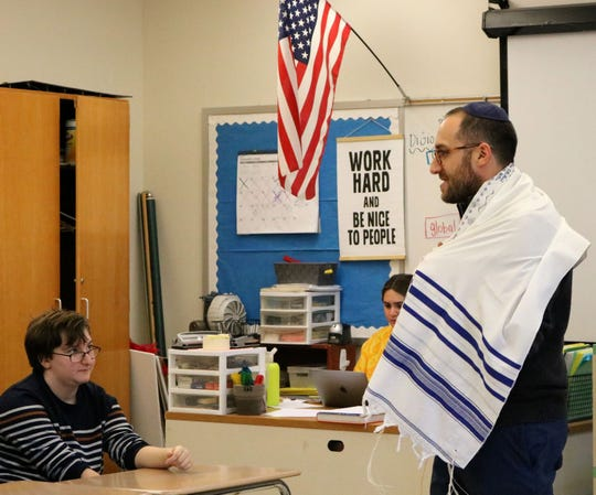 Rabbi Ethan Prosnit of Temple Emanu-El dons a tallit to demonstrate the Jewish people's commitment to a prayerful life.  He visited Cathy Luis' Comparative Religions class on Friday, Jan. 17, at Westfield High School.