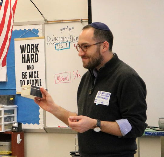 During a visit on Friday, Jan. 17, to a Westfield High School Comparative Religions class, Rabbi Ethan Prosnit of Temple Emanu-El explains the use of a Tzedakah box as part of the Jewish faith's commitment to acts of loving kindness, including collecting money for others in need.