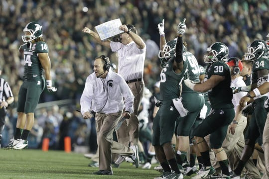 Michigan State coach Mark Dantonio and players celebrate after their defense gets a big stop to force a turnover, effectively sealing the win, against Stanford at the Rose Bowl in Pasadena, Cali. on Wednesday, Jan. 1, 2014.