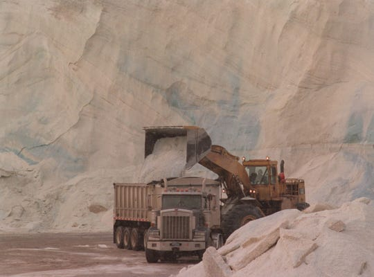 A front-end loader pours road salt into a salt hauler near the stockpile at the Detroit Salt Company in Detroit on Tuesday, Dec. 19, 2000.