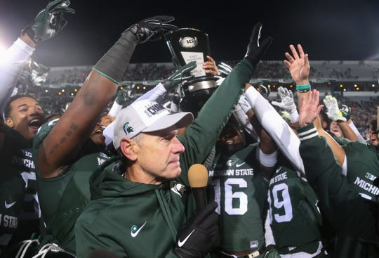 Michigan State coach Mark Dantonio talks to fans after his team received the Big Ten East division trophy after beating Penn State, 55-16, on Nov. 28, at Spartan Stadium.