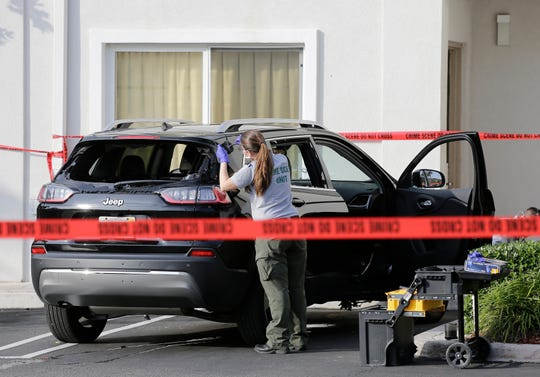 A forensic technician works on the vehicle authorities say officers fired shots at, that breached security at President Donald Trump's Mar-a-Lago resort in Palm Beach, Friday in West Palm Beach, Fla.