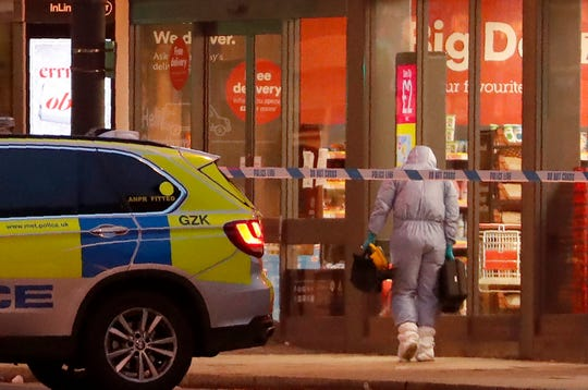 A police forensic officer works near the scene after a stabbing incident in Streatham London, England, Sunday.