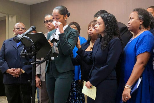 In this Sept. 25, 2019 file photo, Jazmyne Childs, center, cries during a news conference in Raleigh, N.C., as she describes the sexual harassment she says she endured while employed by the North Carolina chapter of the NAACP. Childs is suing the national NAACP group and her ex-supervisor, the Rev. Curtis Gatewood, according to a lawsuit filed Monday, Feb. 3, 2020.