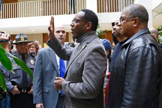 In this Dec. 15, 2019 file photo, Rev. Curtis Gatewood, with the North Carolina chapter of the NAACP, raises a hand as he is confronted by General Assembly police at a demonstration during a special session of the North Carolina Legislature in Raleigh, N.C.