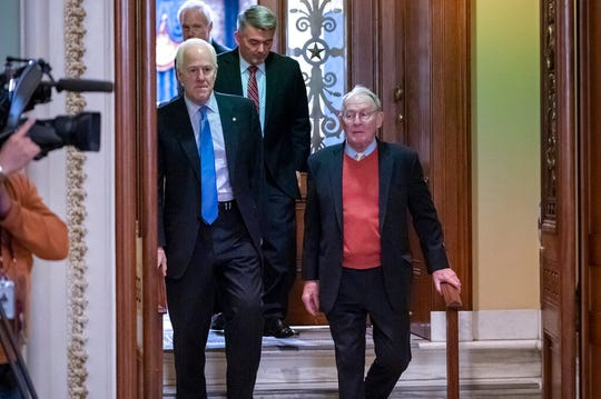 Sen. John Cornyn, R-Texas, left, walks with Sen. Lamar Alexander, R-Tenn., right, joined at rear by Sen. Cory Gardner, R-Colo., leave the chamber after the Senate voted to not allow witnesses in the impeachment trial of President Donald Trump Friday, Jan. 31, 2020