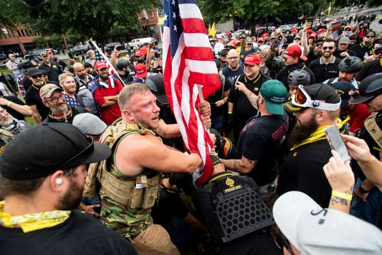 """Joseph Oakman and fellow Proud Boys plant a flag in Tom McCall Waterfront Park during an """"End Domestic Terrorism"""" rally in Portland, Ore., on Saturday, Aug. 17, 2019.  (FILE)"""