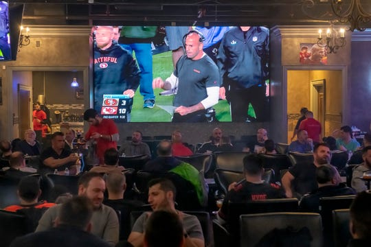 Fans of Dearborn native and San Francisco 49ers defensive coordinator Robert Saleh, seen on screen, cheer him on while watching the Super Bowl at the Lava Lounge Too in Dearborn Heights on Sunday.