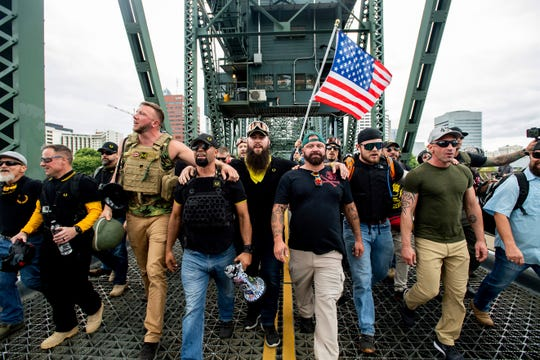 """FILE - In this Aug. 17, 2019 file photo, members of the Proud Boys and other right-wing demonstrators march across the Hawthorne Bridge during an """"End Domestic Terrorism"""" rally in Portland, Ore., on Saturday, Aug. 17, 2019. The group includes organizer Joe Biggs, in green hat, and Proud Boys Chairman Enrique Tarrio, holding megaphone."""