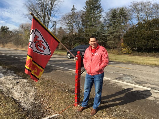 Wearing a Kansas City Chiefs sweatshirt over a Chiefs T-shirt, Michael Casey-Palmisano poses with the team flag that's become a familiar sight for thousands of drivers.