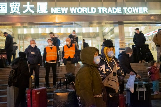 Evacuees gather on the steps of the New World Trade Tower Hotel before an evacuation flight for EU nationals in Wuhan in central China's Hubei Province.